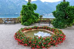 Small pond ornamented with red flowers. Villa del Balbianello green garden royalty free stock images