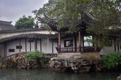 Inside of the administrator garden in China during rainy weather. Small pond with rocks around and gazebo are typical architectonical elements of traditional Royalty Free Stock Photography