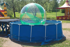 Small pool with big ball. Small children pool with big transparent ball in recreation place royalty free stock photo