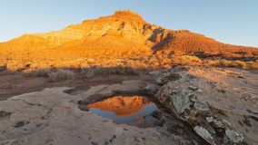 A small pool of rainwater reflects Gooseberry mesa in Southern Utah royalty free stock photography