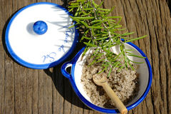 Small porcelain dish with salt. Small porcelain dish with fleur de sel and a rosemary twig on a rustic wooden table Stock Photos