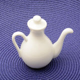 Small porcelain jug on blue base. Beautiful white pitcher on blue woven surface Stock Photography