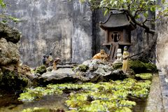 Small porcelain statues in Bonsai scene stock images