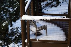 Melting Snow On Small Wooden Porch With Chair. Small Porch With Snow On Chair And Rails Melting With Trees In Background Stock Image