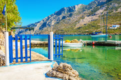 Small port with boat and blue gate, Greece Royalty Free Stock Images