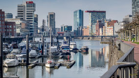 A small port in Duesseldorf at the Rhine river. A small port in Duesseldorf at the Rhine river in a cold and sunny winter day. There are buildings and ships Royalty Free Stock Images