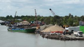Small Port at Mekong River. Editorial: Ca Mau, Vietnam. Small port at Mekong River. Cranes working, loading and unloading ships and truck. Advertisement on stock video footage
