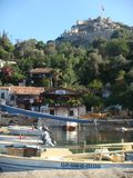 Small port with in distance an old fortress on a mountain in Turkey. royalty free stock photography