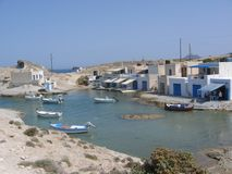 A small port of fishermen to Milos Island in Greece. A small port with white houses with blue doors. Travel destination. Holiday. Small boats. Fishing boats Stock Photos