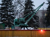 Small portable crane at plumbing pipelaying construction site. City pipeline facility infrastructure repair in progress. with attention red light on wooden stock photo