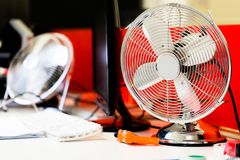 Small, portable switched off fan on desk in office. Horizotal close up, low angle perspective from desk level Royalty Free Stock Photo