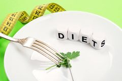 Small portion of food on big plate close-up. Small green parsley leaf on white plate with fork and knife and text diet on the. Background of a measuring tape stock photos