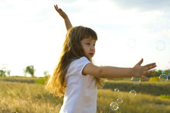 Small positive girl catches soap bubbles Stock Photography