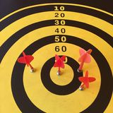 Dart board with red arrow Stock Photos
