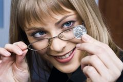 So small, so powerful. Portrait of smiling blond businesswoman in glasses staring at small silver coin Stock Image