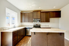 Small yet practical kitchen with brown cabinets and tile marble tops. Northwest, USA royalty free stock photo