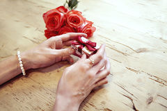 Small present box with bow in woman hands. Bracelet of pearls on hand. focus on bow. Red roses flowers behind on wooden table. Stock Photo