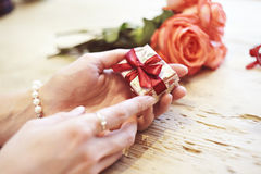 Small present box with bow in woman hands. Bracelet of pearls on hand. focus on bow. Red roses flowers behind on wooden table. Royalty Free Stock Image