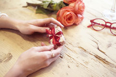 Small present box with bow in woman hands. Focus on bow. Red roses flowers behind on wooden table. St. Valentine`s day concept Royalty Free Stock Photos