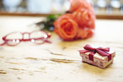 Small present box with bow on wooden table. Focus on bow. Red roses flowers behind on wooden table. St. Valentine`s day concept. B Stock Image