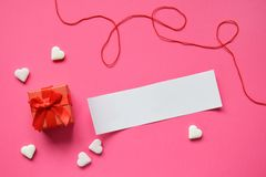 Small present box with an empty paper for your text on pink background. Valentines Day Gift or greeting card concept stock image