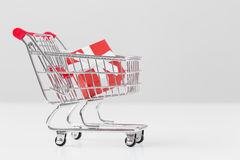 Small present box in miniature shopping cart model Stock Photos