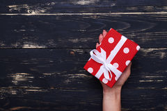 Small present box in woman hand over shabby background Stock Photos