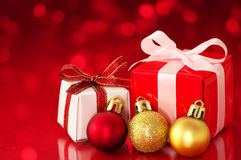 Small presents on red sparkle background. Stock Photos