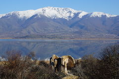 Small Prespa Lake, Agios Achillios island, the ruins of St. Achillius, Greece. Picturesque Small Prespa Lake with surrounding mountains, Agios Achillios island Royalty Free Stock Photography