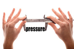 Small pressure. Color horizontal shot of two hands holding a caliper and measuring the word pressure Royalty Free Stock Photography