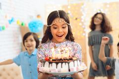 Small pretty girl with pendant chain on her head holds cake with candles at celebration of birthday. royalty free stock photos