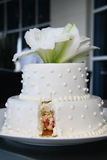 Small Pretty Wedding Cake- Modern- Cut. Small two tire white wedding cake with white flowers on top. Cut on bottom Stock Photo