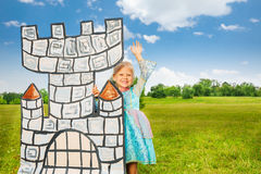 Small princess stands behind drawn tower and waves Stock Photos