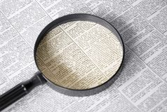 Small print. Trouble reading small print? Magnifying glass on printed paper Royalty Free Stock Image