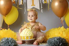 Little girl with brown eyes with a bandage on her head and a beautiful dress crawling on the floor next to balloons and a cake stock images