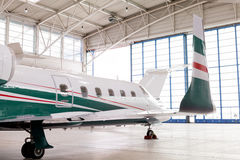 Small private corporate jet in a hangar. Small private corporate jet with green, red and white markings parked in a hangar at an airport, close up angled view of Stock Photos