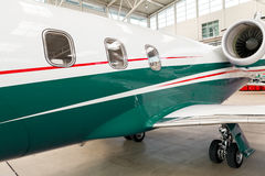 Small private corporate jet in a hangar. Small private corporate jet with green, red and white markings parked in a hangar at an airport, close up angled view of Royalty Free Stock Photography