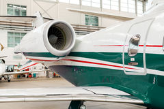Small private corporate jet in a hangar. Small private corporate jet with green, red and white markings parked in a hangar at an airport, close up angled view of Royalty Free Stock Photos