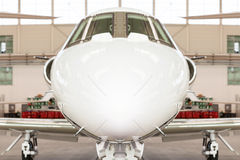 Small private corporate jet in a hangar Stock Photos