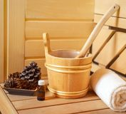 Small private Finnish sauna setting with water bucket, oil essence, cones, hot stones and white towel on wooden background. royalty free stock image