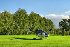 Small private helicopter on grass against mountain Stock Photo