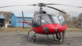 Small private helicopter. Red helicopter parked on the airport apron stock video
