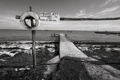 Small Private Jetty. A small private jetty sticks out onto the water. In black and white stock image