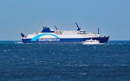 A small private motor boat crosses by an Interislander ferry on the Cook Strait.  stock images