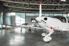 Small private turbo-propeller airplane in hangar. Plane on inspection before flight. Air transportation, front view on turboprop plane royalty free stock photography