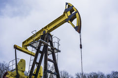 Small private yellow derrick pumps oil. royalty free stock images