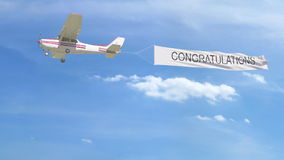 Small propeller airplane towing banner with CONGRATULATIONS caption in the sky. 3D rendering Royalty Free Stock Photography