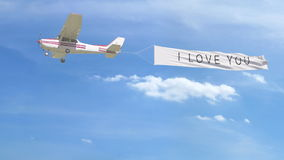 Small propeller airplane towing banner with I LOVE YOU caption in the sky. 3D rendering Royalty Free Stock Photo