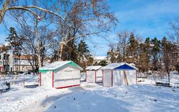 Small public wooden cottage barracks or houses in the park for street vendors or sellers in the city closed in the winter period a. Fter holidays, small private stock photo
