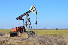 Small Pump Jack in agricultural field Royalty Free Stock Photography